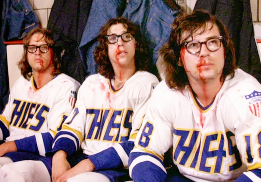"The movie ""Slap Shot"", directed by George Roy Hill. Seen here of the Charlestown Chiefs hockey team, the Hanson Brothers. From left, David Hanson (as Jack Hanson). Steve Carlson (as Steve Hanson), Jeff Carlson (as Jeff Hanson). Initial theatrical release February 25, 1977. Screen capture. Copyright © 1977 Universal Pictures. Credit: © 1977 Universal Pictures / Courtesy: Pyxurz."